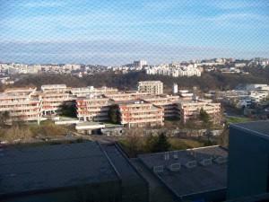 """Výhled z okna pokoje na koleji (14. nebo 15. patro, záleží, kterým výtahem jedete). To """"divné"""" na fotografii není závada ani žádný speciální filtr, ale síť proti holubům, kteří mají velice rádi balkony (souboj holub vs. síť – 1:0)"""